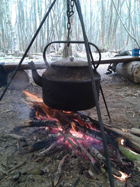 Kirtley campfire kettle suspended over fire from tripod